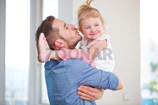 Mann küsst Kind auf die Wange