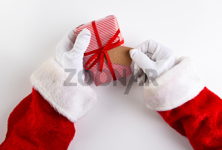 Overhead shot of Santa Claus hands holding a Christmas Present wrpped in red striped paper with a blank gift tag.