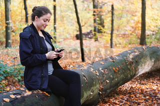 young woman using mobile smartphone outdoors in woods