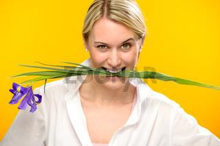 Woman bite spring iris flower between teeth