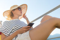 Beautiful, romantic blonde woman on summer vacations traveling by cruse ship ferry boat holding and using mobile phone. Summer vacation lifestyle