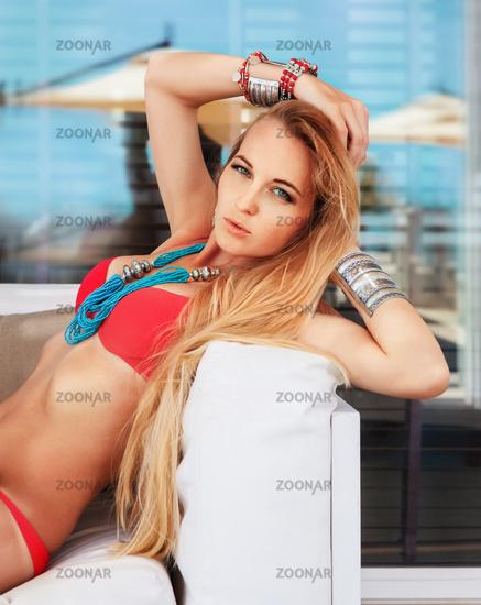 Sexy young blond woman posing in a red bikini