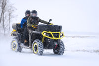 Driving with quad vehicle in the snow in winter