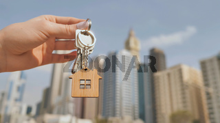 Real estate purchase concept. The girl holds the keys to a new house on the background of a Dubai skyscraper.