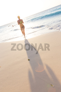 Happy woman enjoying in summer, running joyfully on tropical beach in sunset. Beautiful caucasian model wearing bikini on vacations on sandy beach. Footprints in sand. Copy space