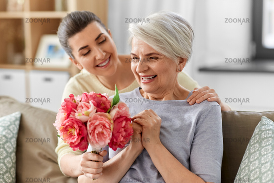 adult daughter giving flowers to old mother