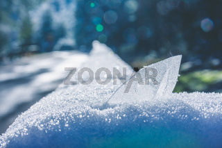 Transparent crystal half buried in a snowdrift
