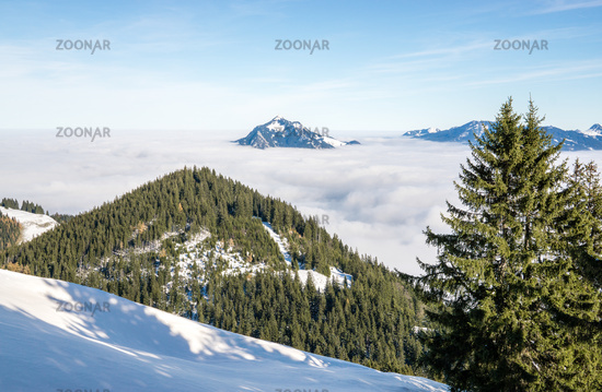 Amazing View from Snow Mountain to snowy Mountain Range above inversion foggy cloud layer. Above the clouds on Rangiswangerhorn, Allgau, Bavaria, Germany.