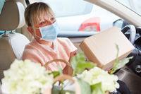 Frau mit Mundschutz prüft Paket im Innenraum ihres Autos