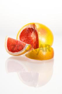 Angeschnittene Grapefruit mit Spiegelung vor weißem Hintergrund