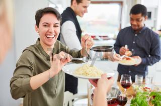 Junge Frau serviert Nudeln mit Tomatensauce in WG
