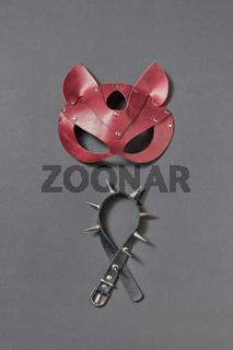 Leather collar with sharp spines and cat BDSM mask on a black background.