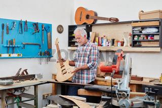 Senior Handwerker baut E-Gitarre in Werkstatt