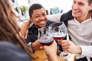 Männer als Freunde beim Wein trinken zusammen