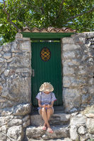 Beautiful young female tourist woman wearing big straw hat using moile phone, sitting in front of white vinatage wooden door and textured stone wall at old Mediterranean town