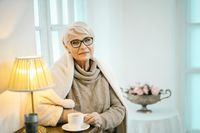 Old Woman Relaxing At Home And Drinking Tea