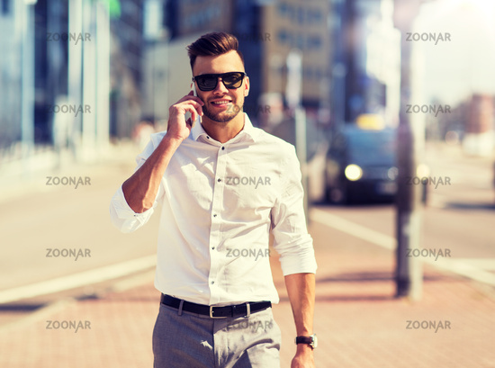 happy man with smartphone calling on city street
