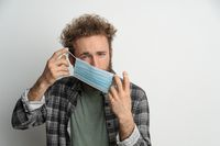 Young man holding protective sterile medical mask in front of face to protect coronavirus, with curly hair, wearing plaid shirt and olive t-shirt under. White background