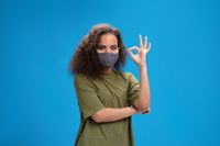 Saying OK using her hands to communicate pretty african american girl in reusable protective face mask. Curly haired young woman showing hello sign talking on camera isolated on blue background