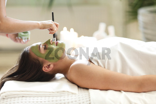 Beautiful relaxed woman having clay face mask