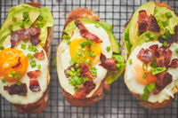 Breakfast concept. Tasty delicious homemade toasts with fried egg, bacon, avocado, lettuce and chive