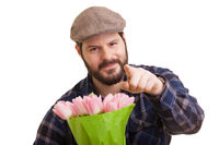 Bearded young handsome man with pointed indexfinger holding a bouquet of pink tulips