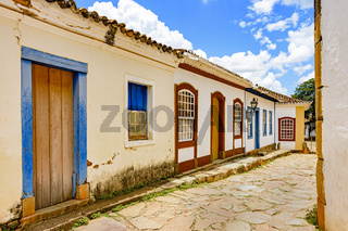 Old cobbled street with houses in colonial architecture