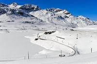 Die Rhätische Eisenbahn am winterlichen Bernina Pass, Engadin, Graubünden, Schweiz