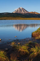 Autumn volcanic landscape, evening view of volcano and reflection of mountains peak in beautiful alpine lake