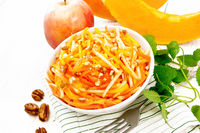 Salad of pumpkin and apple with nuts in bowl on light board