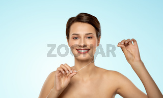 happy young woman with dental floss cleaning teeth
