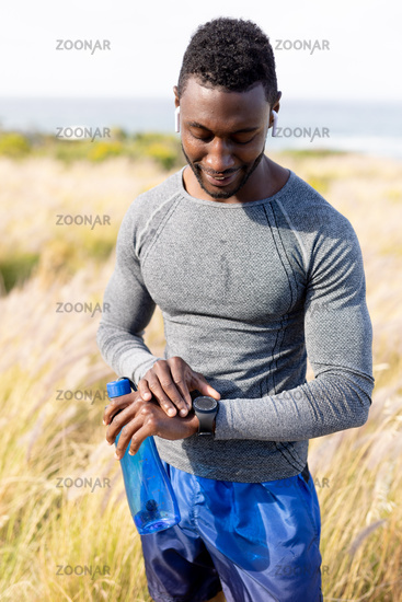 Portrait of fit african american man in sportswear using smartwatch holding water in tall grass