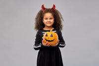 girl in halloween costume with jack-o-lantern