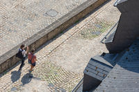 View man and woman walking over medieval pavement Luxembourg city