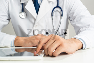 Close up of doctor hands using tablet computer
