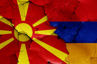 flags of North Macedonia and Armenia painted on cracked wall