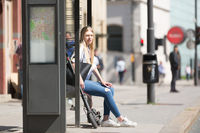 Casual caucasian teenager commuter with modern foldable urban electric scooter sitting on a bus stop bench waiting for metro city bus. Urban mobility concept
