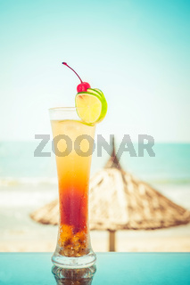 Long Island cocktail with fruits decoration at tropical ocean beach with umbrella. Vintage style, hipster colors image with copy space for party invitation text