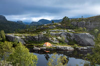 Tourist tent on the shore of a lake in the mountains. Beautiful Nature Norway natural landscape.