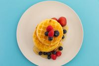 Stack of pancakes with berries and honey on plate on blue background