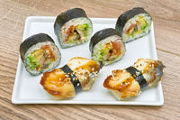 sushi and rolls on a plate on a wooden background