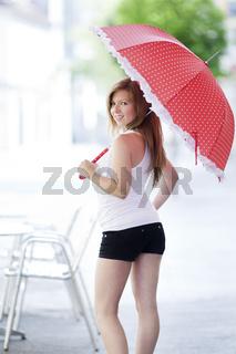 Junge Frau mit Schirm blickt über die Schulter
