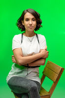 Female portrait on chroma key in studio. Serious brunette woman in white t-shirt posing on green background