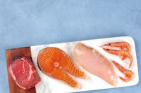 Main proteins. Fresh raw meat, fish, chicken fillet, and seafood, shot from above with copy space