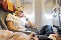 Tired blonde casual caucasian lady napping on uncomfortable seat while traveling by airplane.