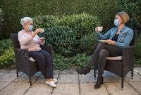Seniorin und Tochter mit Mundschutz beim Kaffee trinken im Garten mit Sicherheitsabstand