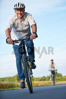 Senioren mit Fahrradhelm fahren Fahrrad