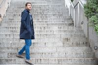 Horizontal portrait of young attractive man standing on steps looking back. Modern and stylish guy holds Laptop hands.