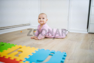 Adorable baby lying face down on the wooden floor