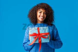 Holidays, winter season and christmas concept. Lovely cute african-american woman wrapped her present to give it boyfriend on valentines day, smiling cheerful, saying happy new year